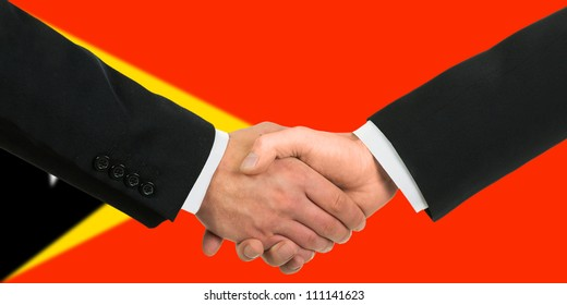 The East Timor flag and business handshake