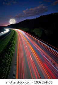 The eastbound lanes of I70 Ohio at night with the full moon on the horizon.