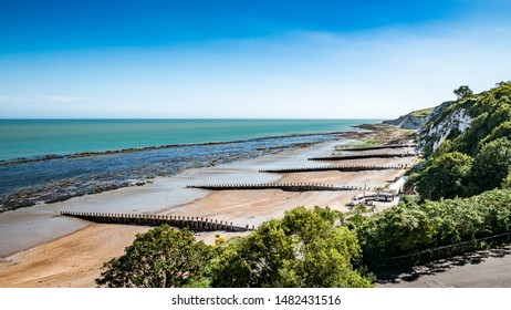 Eastbourne beach, Sussex, England. A bright, summer view west along the Eastbourne promenade and sea front towards the white cliffs and South Downs in the distance.