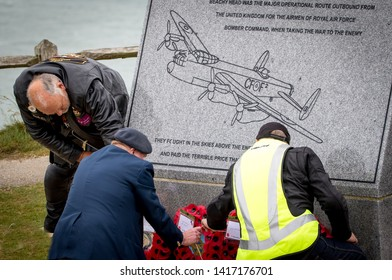 Eastbourne, Beachy Head, UK. 5th June 2019. In preparation for the D Day DC3 flypast, veterans place Poppy wreaths around the Bomber Command memorial  that sits upon this South Coast Cliff top.