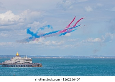 "Eastbourne, East Sussex, England, UK - 08/17/2018. Airbourne (Eastbourne International Airshow). Five of the Red Arrows performing the ""Rollbacks"" manoeuvre whilst crossing by Eastbourne's pier."