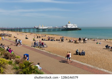 EASTBOURNE, EAST SUSSEX, ENGLAND, UK-APRIL 22nd 2018: People walking on the seafront and enjoying the beach in sunny Eastbourne, East Sussex, on Sunday 22nd April 2018
