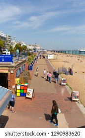 EASTBOURNE, EAST SUSSEX, ENGLAND, UK-APRIL 22nd 2018: People walking on the promenade in warm spring weather in the coast town of Eastbourne, East Sussex, on Sunday 22nd April 2018