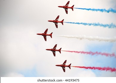 "EASTBOURNE, ENGLAND - AUGUST 16: RAF aerobatic display team ""The Red Arrows"" perform at an airshow on August 16, 2009 in Eastbourne, Sussex."