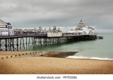 Eastbourne pier and beach. English seaside victorian amusement arcade and tourist landmark.