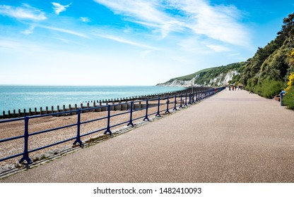 Eastbourne promenade, East Sussex, England. A bright, summer view west along the sea front towards the white chalk cliffs and South Downs.