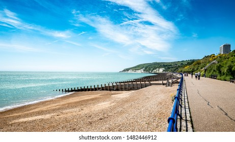 Eastbourne promenade and the South Downs, England. A bright, summer view west along the Eastbourne promenade and sea front towards the white cliffs and South Downs in the distance.