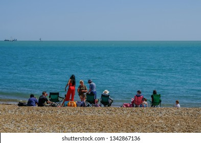 Eastbourne, Sussex, England, UK - August 1, 2018: Families picnicing on beach in Eastbourne.  Taken on sunny blue sky summer's afternoon, shows rear view of people sitting, standing near waters edge.