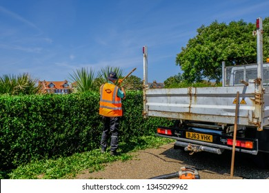 Eastbourne, Sussex, England, UK - August 1, 2018: Workmanj raking the trimmings of a newly cut edge.  Wearing a hi-viz jacketand backend of truck.