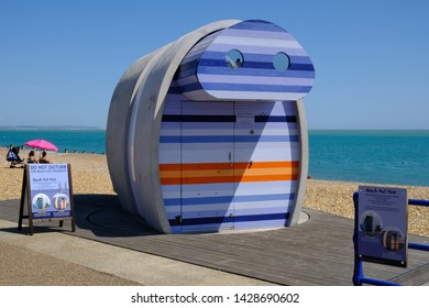 Eastbourne, Sussex, England, UK - August 1, 2018:  Brightly coloured modern beach hut for hire on the front at Eastbourne's beach.