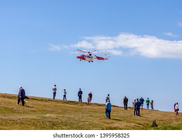 Eastbourne, Sussex, UK. 12th May 2019. Tourists watch from teh cliff edge as the coastguard helicopter searches the cliffs