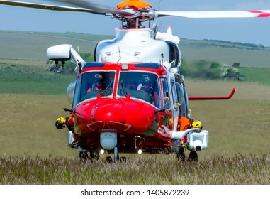 Eastbourne, Sussex, UK. 23rd May 2019. Winchmen hang out either side of the coastguard helicopter as it lands at Beachy Head