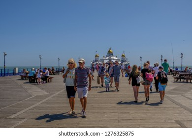 Eastbourne, Sussex, UK - August 1, 2018: People strolling on the pier at Eastbourne.  Taken on a bright sunny blue sky summer's day.