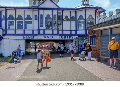 Eastbourne, Sussex, UK - August 1, 2018:  Fish and chips restaurant at the beginning of the pier.  People strolling on the promenade which goes underneath the pier.