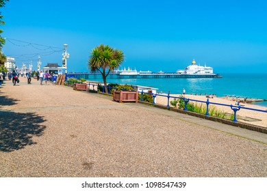 EASTBOURNE, SUSSEX, UK - MAY 20,2018:People stroll along promenade in Eastbourne, seaside resort in East Sussex. The seafront is lined with Victorian hotels, the 19th-century Pier and a 1930 bandstand