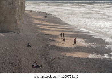 EASTBOURNE, UK - 21 SEPTEMBER 2018: Tourists on the beach on stormy day at Birling Gap near Eastbourne