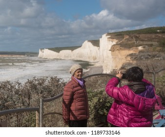 EASTBOURNE, UK - 21 SEPTEMBER 2018: Asian tourists taking snapshot on stormy day at Birling Gap near Eastbourne