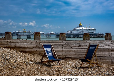 Eastbourne, UK - May 7 2019: deckchairs with eastbourne pier