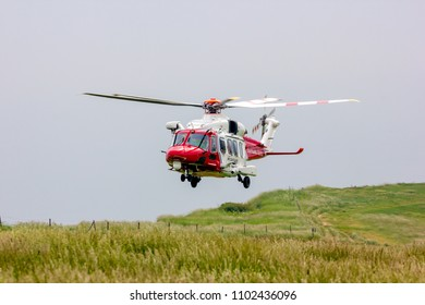 Eastbourne, United Kingdom. 30th May 2018. Search and rescue helicopter assists coastguard with the recovery of a fall victim from the cliffs at this location