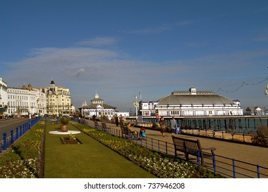 EASTBOURNE, UNITED KINGDOM - FEBRUARY 8, 2009: People walking and sitting on benches on Grand Parade, Eastbourne, East Sussex, by the garden next to the road. In the distance is Eastbourne Pier.
