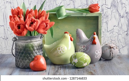 Easter arrangement with bunch of red tulips, ceramic hens and Easter eggs on light wooden background