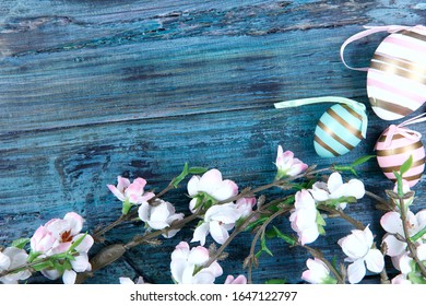 Easter background. At the bottom right of the frame are artificial branches of a blossoming apple tree and three painted eggs. Easter eggs on a blue wooden background. Close-up, free seats, horizontal