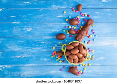 Easter background with chocolate rabbit and a full bowl of Easter eggs