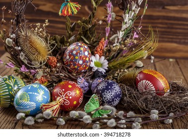 Easter background. colored Easter eggs in the nest and composition of dried flowers and plants. on wooden background. easter theme. happy easter