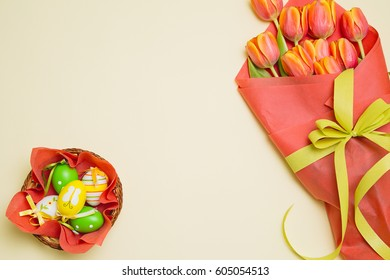 Easter background with colorful eggs in basket and tulip flowers on a yellow background. Top view with copy space