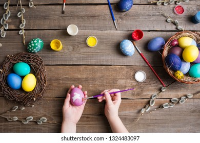 Easter background. colorful eggs in a nest of straw and willow branches and basket on wooden table. the process of painting eggs . children's hands holding an egg and brush. Top view