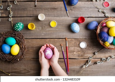 Easter background. colorful eggs in a nest of straw and willow branches and basket on wooden table. the process of painting eggs . children's hands holding an egg. Top view