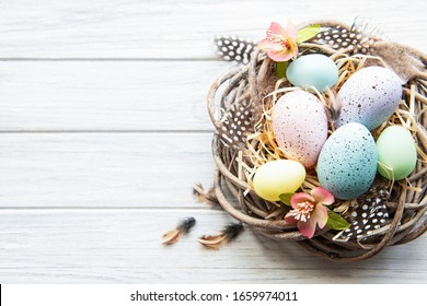 Easter background with colorful eggs in nest  on a white wooden background. Top view with copy space