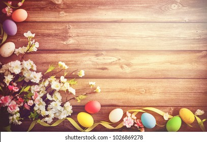 Easter background with colorful eggs and spring flowers. Top view with copy space