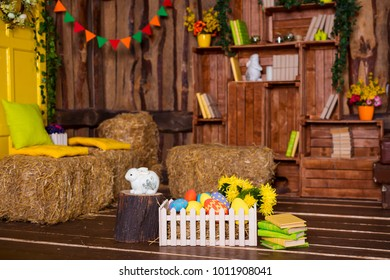 Easter background with colorful eggs, white bunny and yellow flowers over old wood.