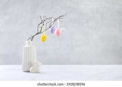 Easter background with copy space for a greeting text, front view of a white modern vase with a branch decorated with Easter eggs