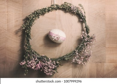 Easter background with Easter egg inside the flower wreath, pastel colours decoration from rope, ribbon and button with wooden background
