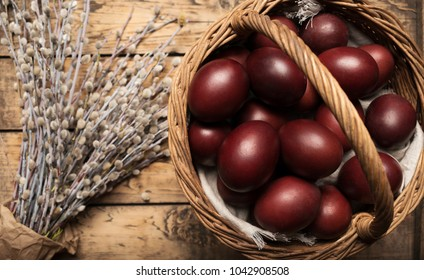 Easter background with Easter eggs in a basket on a wooden background decorated with twigs of withy. Top view with copy space. Orthodox Easter. Flat lay. Natural style. Traditional Russian Easter eggs
