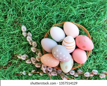 Easter background with Easter eggs in basket over green grass