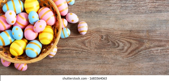 Easter background with eggs and beautiful spring flowers on wooden table.