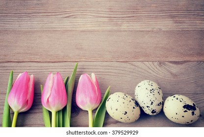 Easter background with eggs and pink tulips. Holiday card with copy space, on old wooden table.