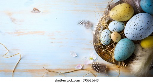 Easter background with Easter eggs and spring flowers. Top view with copy space.