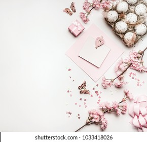 Easter background with flat lay of eggs,gifts, decorations blossom and blank greeting card mock up on white desktop, top view, pink pastel color