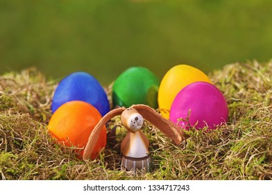 Easter background with a funny easter rabbit and colored eggs, greeting card with copy space