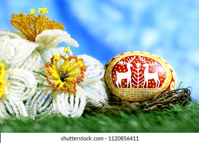 Easter background with Easter hand made egg and spring handmade flowers. With copy space.