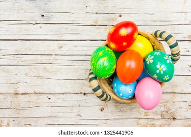 Easter background with handmade colored eggs on nest. Top view and copy space. Festive tradition