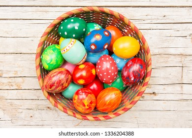 Easter background with handmade colored eggs on nest. Top view. Festive tradition