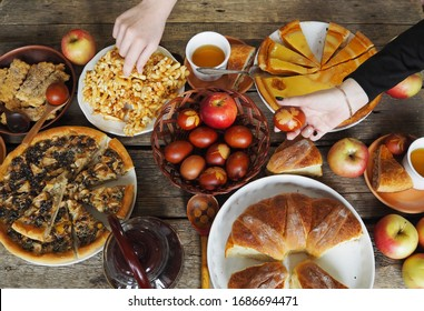 Easter background. Holiday, plentiful food and colored eggs on a wooden background. Guest hands of people over the table.