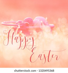 Easter background, with Mini easter eggs in a little pink bucket in the grass. Great for social media campaigns.