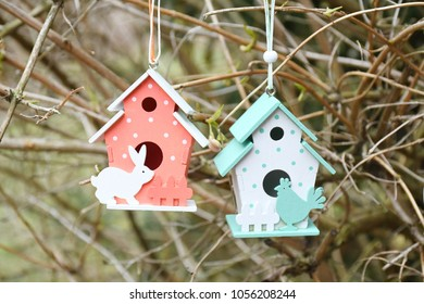Easter background with small red and green ble house hanging on dry tree with background green field,  text copy space, happy and funny season in april.