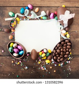 Easter Background  with white blank paper greeting card and chocolate Easter Eggs. Top view